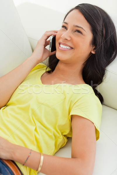 Smiling Latino on the phone while lying on a sofa Stock photo © wavebreak_media