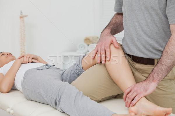 Woman lying on her back while a physiotherapist manipulates her leg in a physio room Stock photo © wavebreak_media