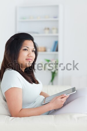 Woman sitting on a couch while holding a tactile tablet in living room Stock photo © wavebreak_media