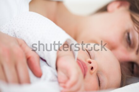 Stock photo: Mother lying with her cute little daughter indoors