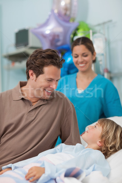 Child lying on a medical bed looking at his father in hospital ward Stock photo © wavebreak_media