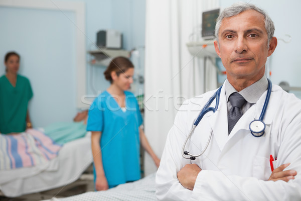 Doctor in hospital room with two nurses and a patient in the background Stock photo © wavebreak_media