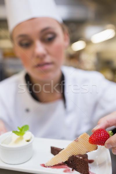 Chef putting strawberry on dessert plate in the kitchen Stock photo © wavebreak_media