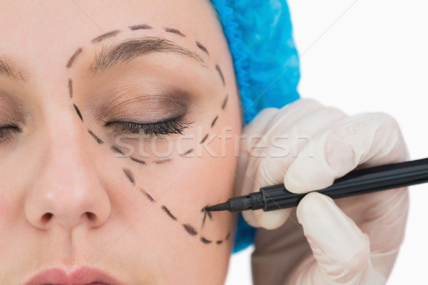 Surgeon writing on the serious woman's face in the white background Stock photo © wavebreak_media