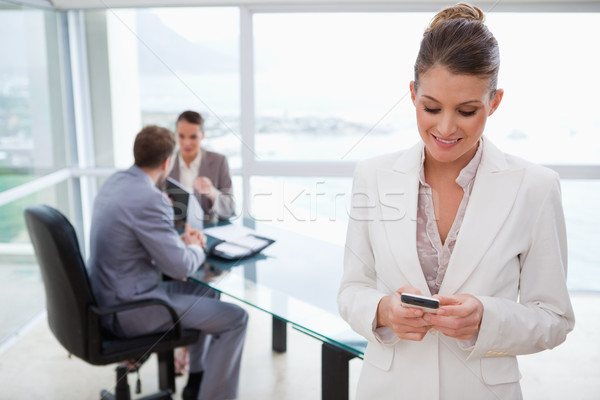 Colleagues in meeting with business woman text  messaging in for Stock photo © wavebreak_media