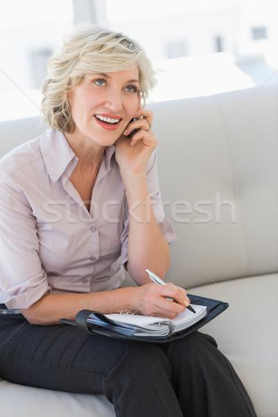 Homme secrétaire journal téléphone portable souriant canapé Photo stock © wavebreak_media