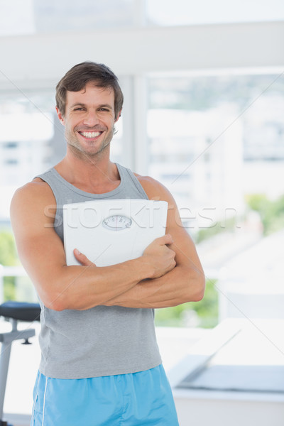 Fit man standing with scale in bright exercise room Stock photo © wavebreak_media
