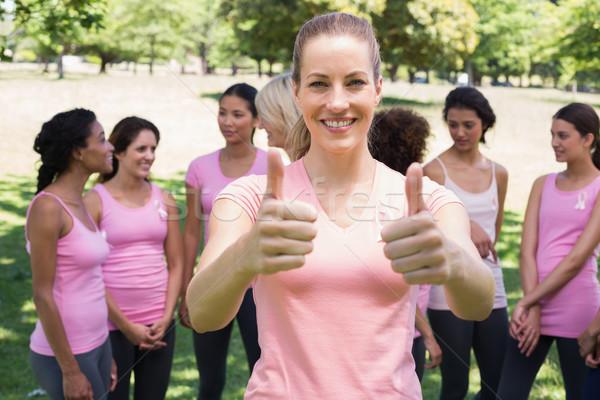 Volunteer gesturing thumbs up at breast cancer campaign  Stock photo © wavebreak_media