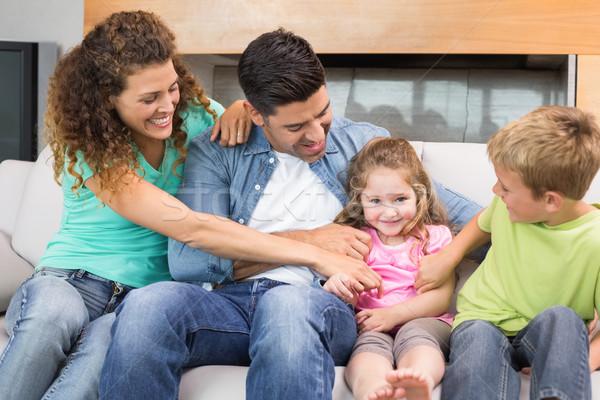 Cute family tickling little girl on the couch Stock photo © wavebreak_media