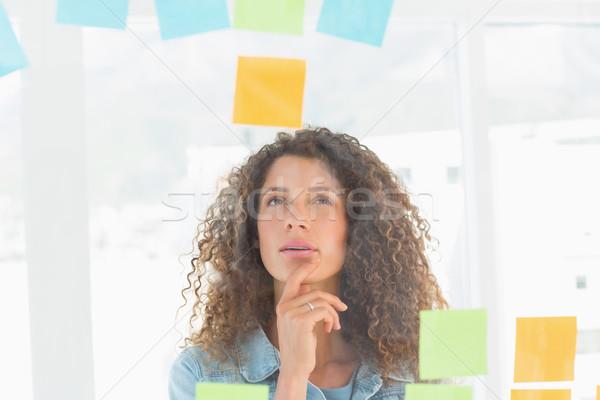 Bastante disenador mirando notas adhesivas ventana Foto stock © wavebreak_media