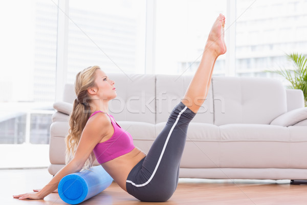 Fit blonde stretching on floor using foam roller Stock photo © wavebreak_media