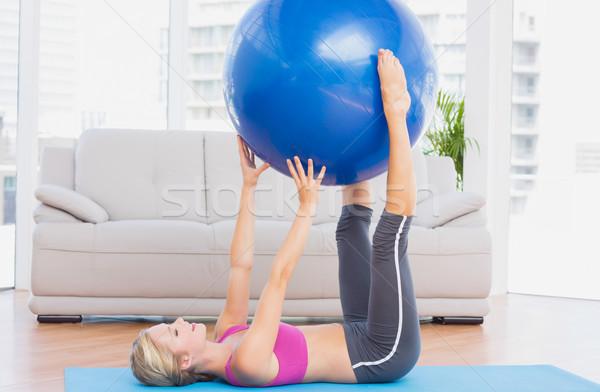 Cheerful fit blonde holding exercise ball between legs Stock photo © wavebreak_media