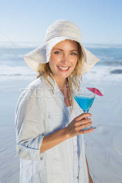 Smiling blonde relaxing by the sea holding cocktail Stock photo © wavebreak_media