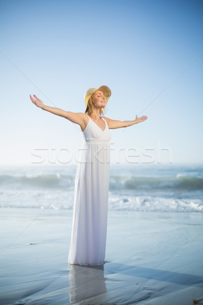 Smiling blonde standing on the beach in white sundress and sunha Stock photo © wavebreak_media
