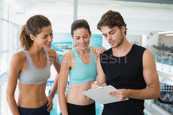 Fit women with trainer taking notes and smiling at camera Stock photo © wavebreak_media