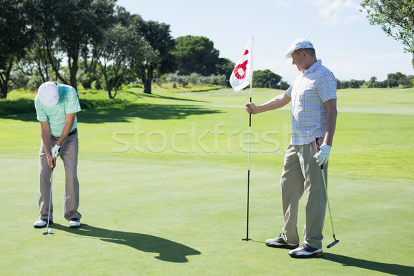Stock photo: Golfer holding eighteenth hole flag for friend putting ball