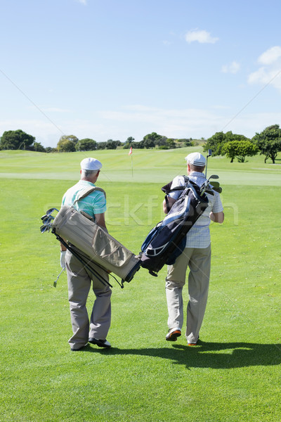 Golfer friends walking and holding their golf bags Stock photo © wavebreak_media
