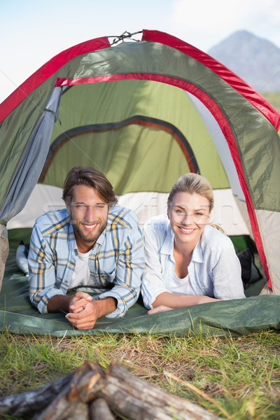 Attractive couple lying in their tent smiling at camera Stock photo © wavebreak_media