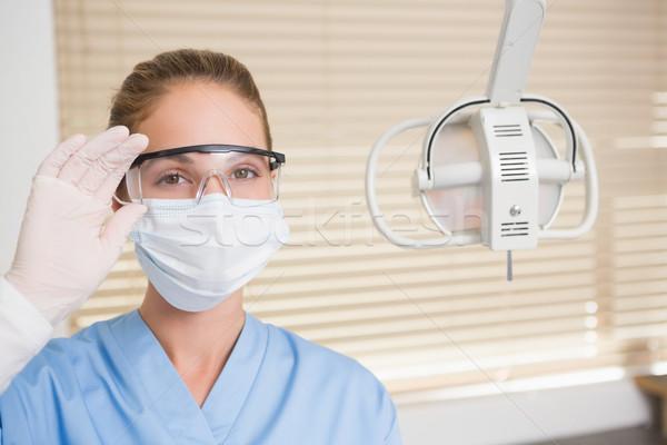 Dentista máscara cirúrgica óculos olhando câmera dental Foto stock © wavebreak_media