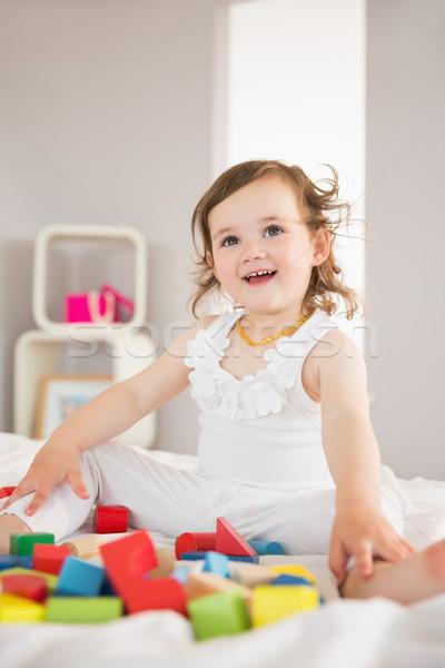 Aranyos lány játszik tömbházak ágy kislány Stock fotó © wavebreak_media