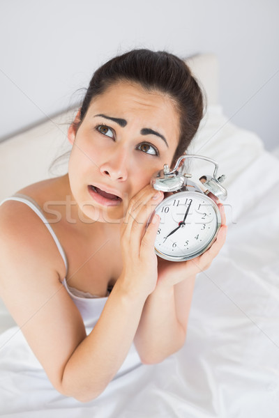 Annoyed woman holding an alarm clock in bed Stock photo © wavebreak_media