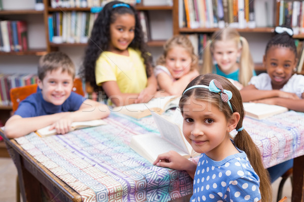 Cute pupils looking at camera in library Stock photo © wavebreak_media