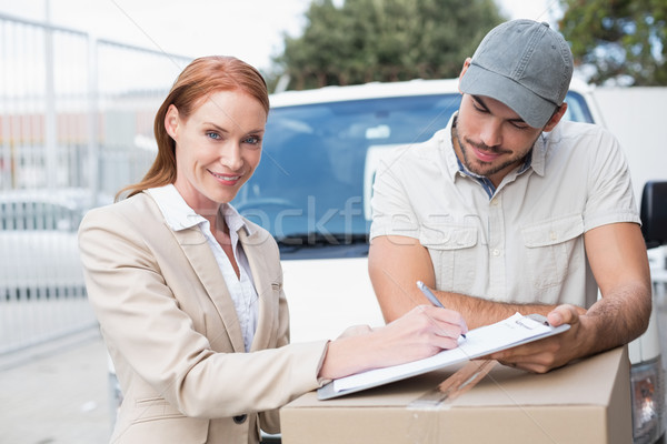 Delivery driver showing where to sign to customer Stock photo © wavebreak_media