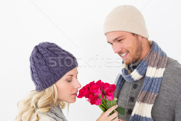 Attractive couple in warm clothing holding flowers Stock photo © wavebreak_media