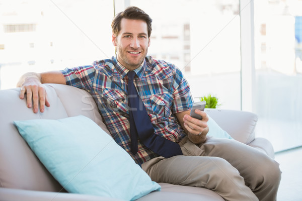 Happy man sitting on the couch sending a text message Stock photo © wavebreak_media