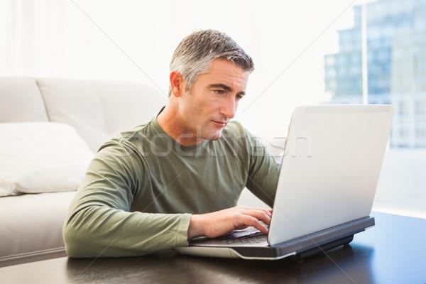 Zagęszczony człowiek siwe włosy za pomocą laptopa domu salon Zdjęcia stock © wavebreak_media