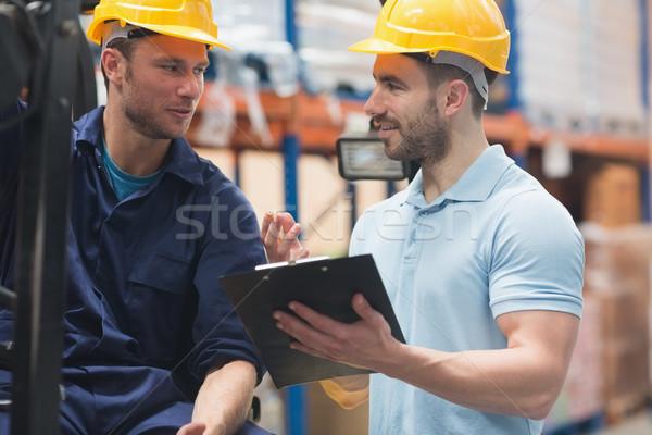 Uśmiechnięty magazynu pracowników mówić wraz człowiek Zdjęcia stock © wavebreak_media