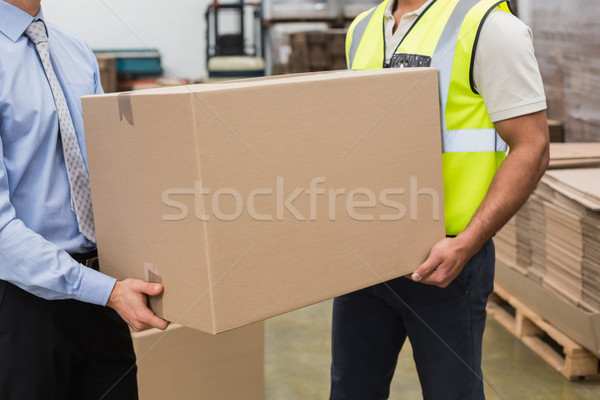 Warehouse worker and manager passing a box Stock photo © wavebreak_media