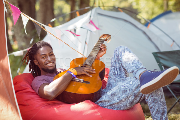 Happy hipster relaxing on campsite playing guitar Stock photo © wavebreak_media