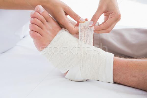 Doctor bandaging her patient leg  Stock photo © wavebreak_media
