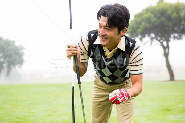 Golfer holding golf ball and club Stock photo © wavebreak_media