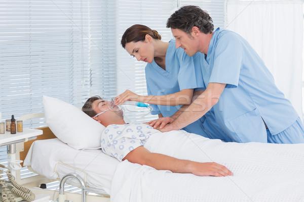 Worried doctors doing heart massage and holding oxygen mask Stock photo © wavebreak_media