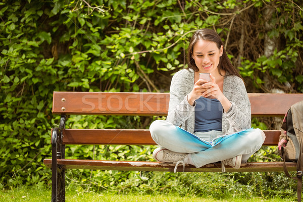 Smiling student sitting on bench text message on her mobile phon Stock photo © wavebreak_media