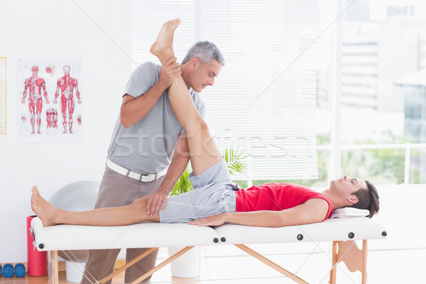 Stock photo: Physiotherapist doing leg stretching to his patient
