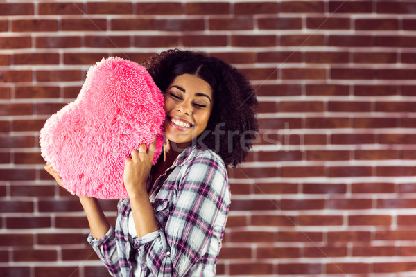 Attractive young woman cuddling with heart-shaped pillow Stock photo © wavebreak_media