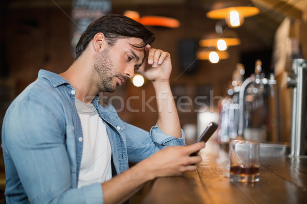 Upset man using mobile at pub Stock photo © wavebreak_media