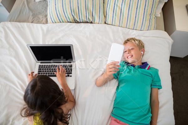 Testvérek mobiltelefon laptop ágy hálószoba számítógép Stock fotó © wavebreak_media