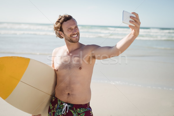 Smiling shirtless man taking selfie with surfboard at beach Stock photo © wavebreak_media