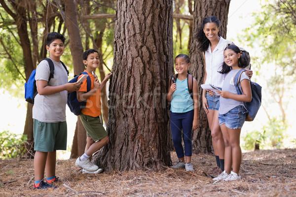 Happy students and teacher standing by tree Stock photo © wavebreak_media