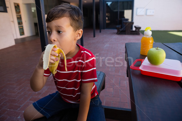 Boy looking away while eating banana at table Stock photo © wavebreak_media