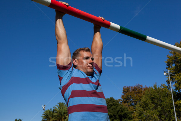 Low angle view of rugby player hanging on goal post against clear sky Stock photo © wavebreak_media