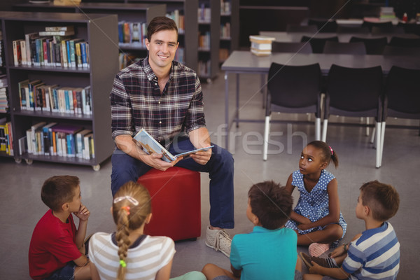 Happy teacher teaching schoolkids in library Stock photo © wavebreak_media