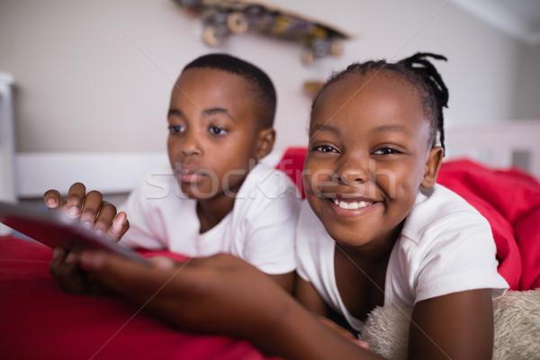 Derűs lány fivér mobiltelefon ágy otthon Stock fotó © wavebreak_media