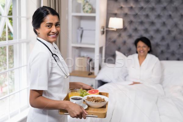 Portrait of nurse serving breakfast to patient at home Stock photo © wavebreak_media