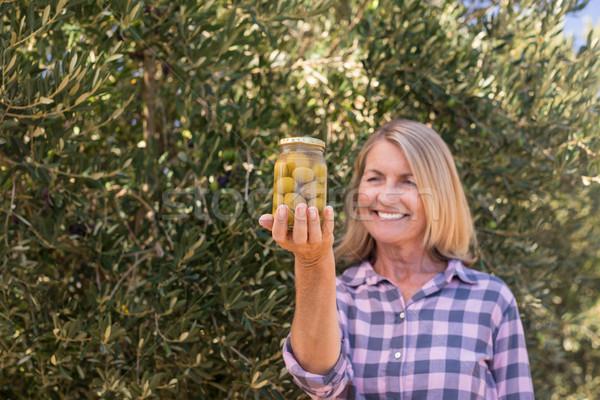 Happy woman examining pickled olive in farm Stock photo © wavebreak_media
