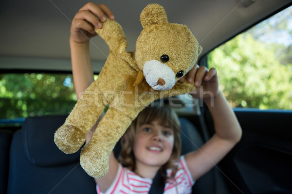 Teenage girl playing with teddy bear in back seat of car Stock photo © wavebreak_media